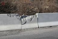 Betonové svodidlo New Jersey po zásahu skalního bloku.