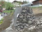 Ochranný val chránící bytovou zástavbu provedený z materiálu Terramesh.
