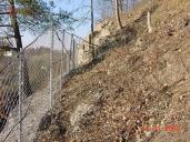 Ukázka užití lehkého záchytného plotu s využitím ocelové dvouzákrutové sítě Maccaferri – detail zpevnění lany a kotvení sloupku do svahu.